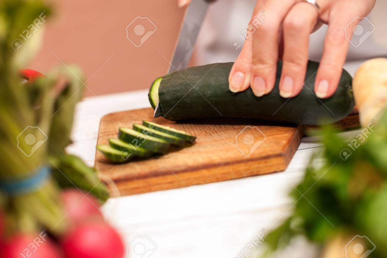 housewife cutting cucumber with a knife in the kitchen on cutting