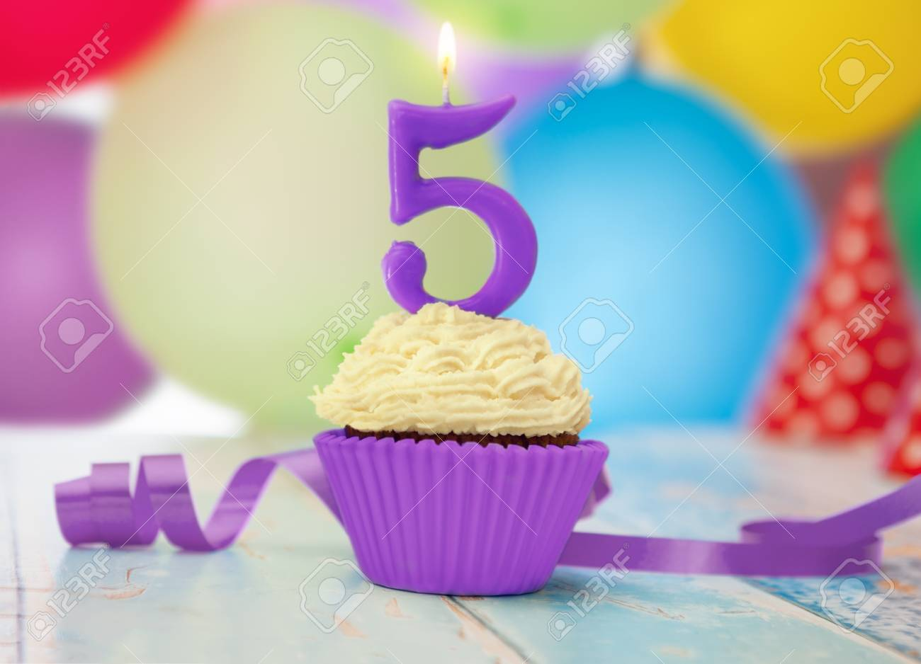 Birthday Candle With Number 5 On Cupcake Balloons In The Background Stock Photo