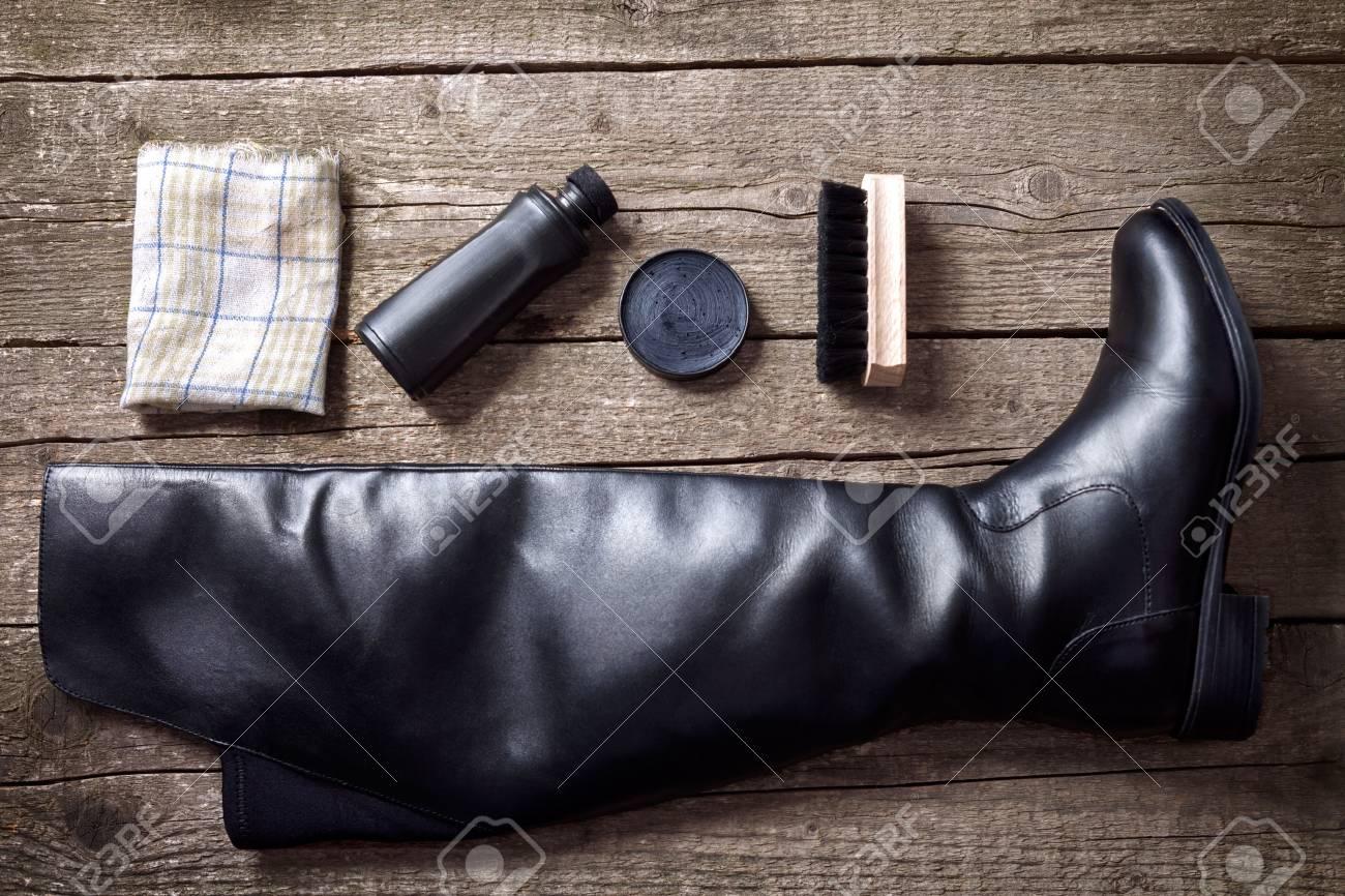 Schwarzer Stiefel, Politurcreme, Bürste und Stoff auf Holzuntergrund  Standard-Bild - 87525959 ed8f6bbf2e
