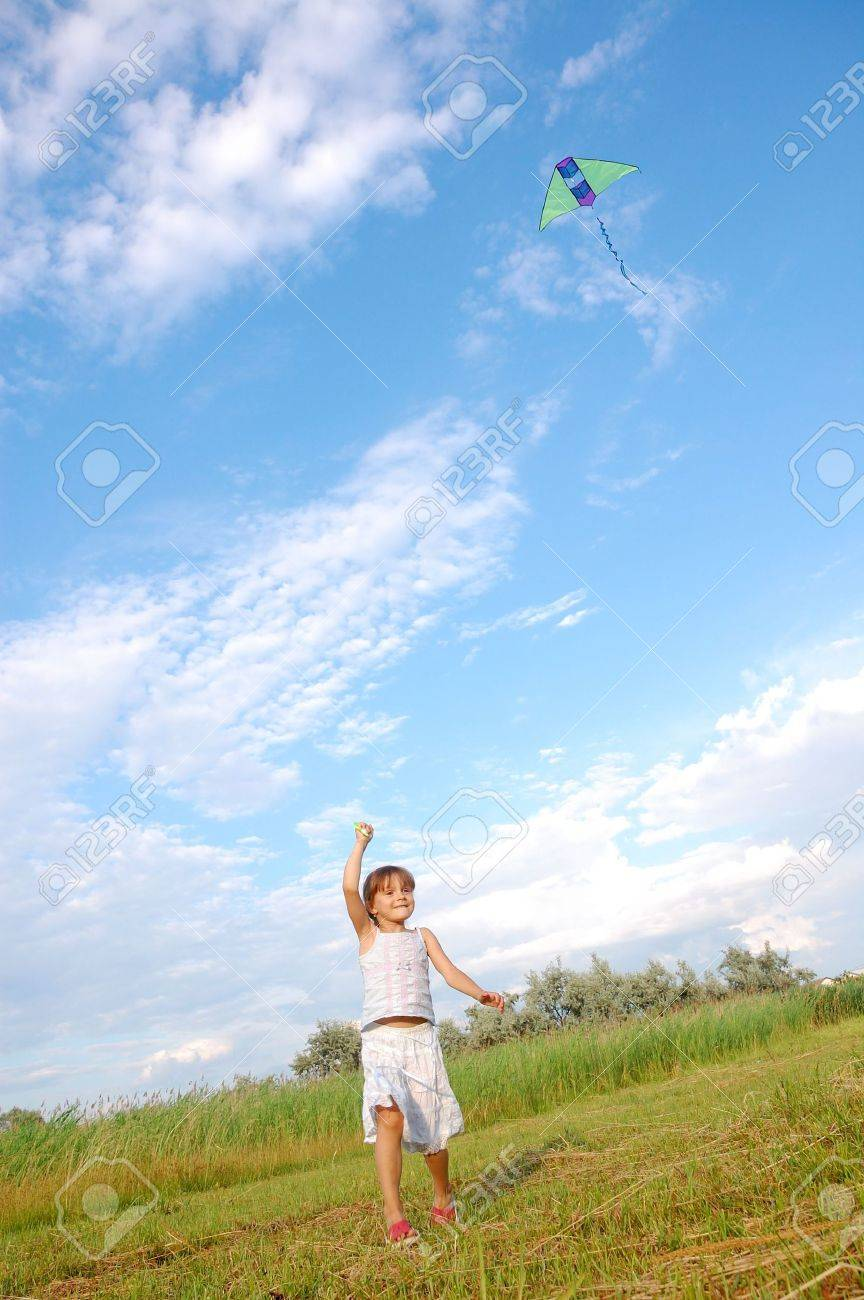 girl running and flying a kite in the meadow Stock Photo - 5438997