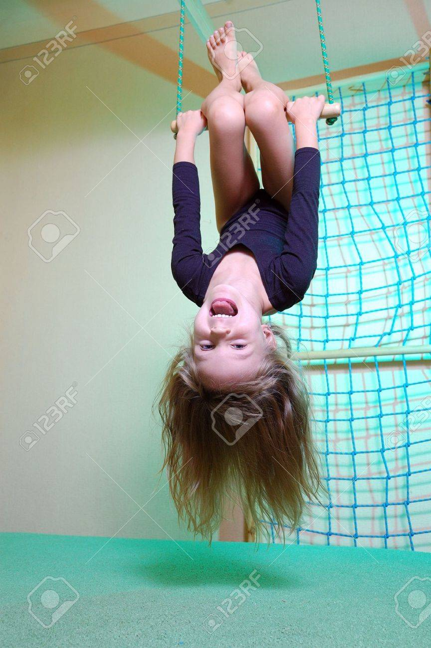 little 5 year old girl wearing a black leotard playing with her home wooden gym Stock Photo - 5483138
