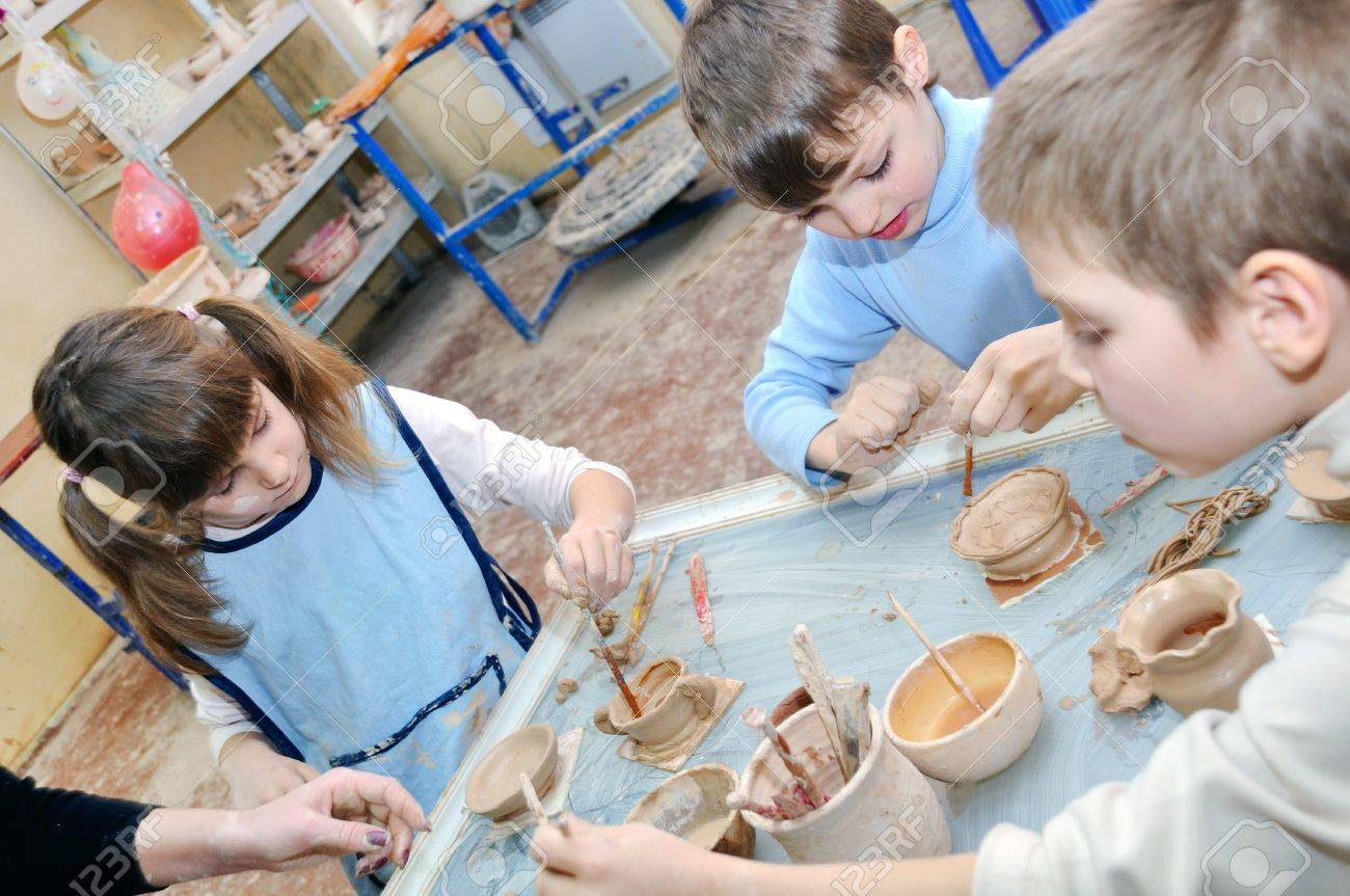 group of children shaping clay at the pottery studio Stock Photo - 14549758