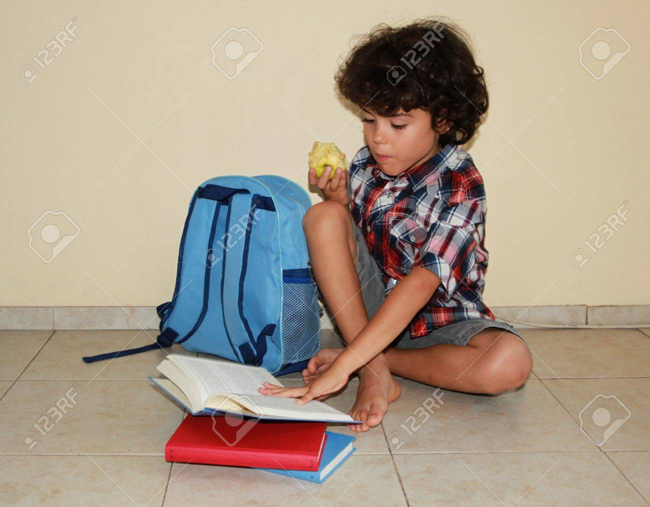 A beautiful child with apple sitting on the floor and reading a book surrounded with blue bag and books Stock Photo - 14920116