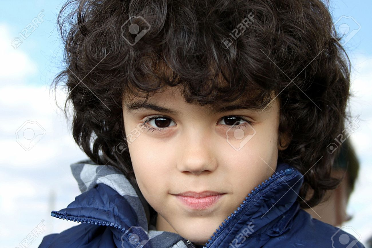 Outdoor Portrait Of A Beautiful Boy With Long Curly Hair Stock Photo