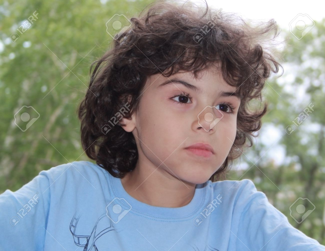 Cute Little Boy With Curly Hair Is Posing In Front Of Camera Stock
