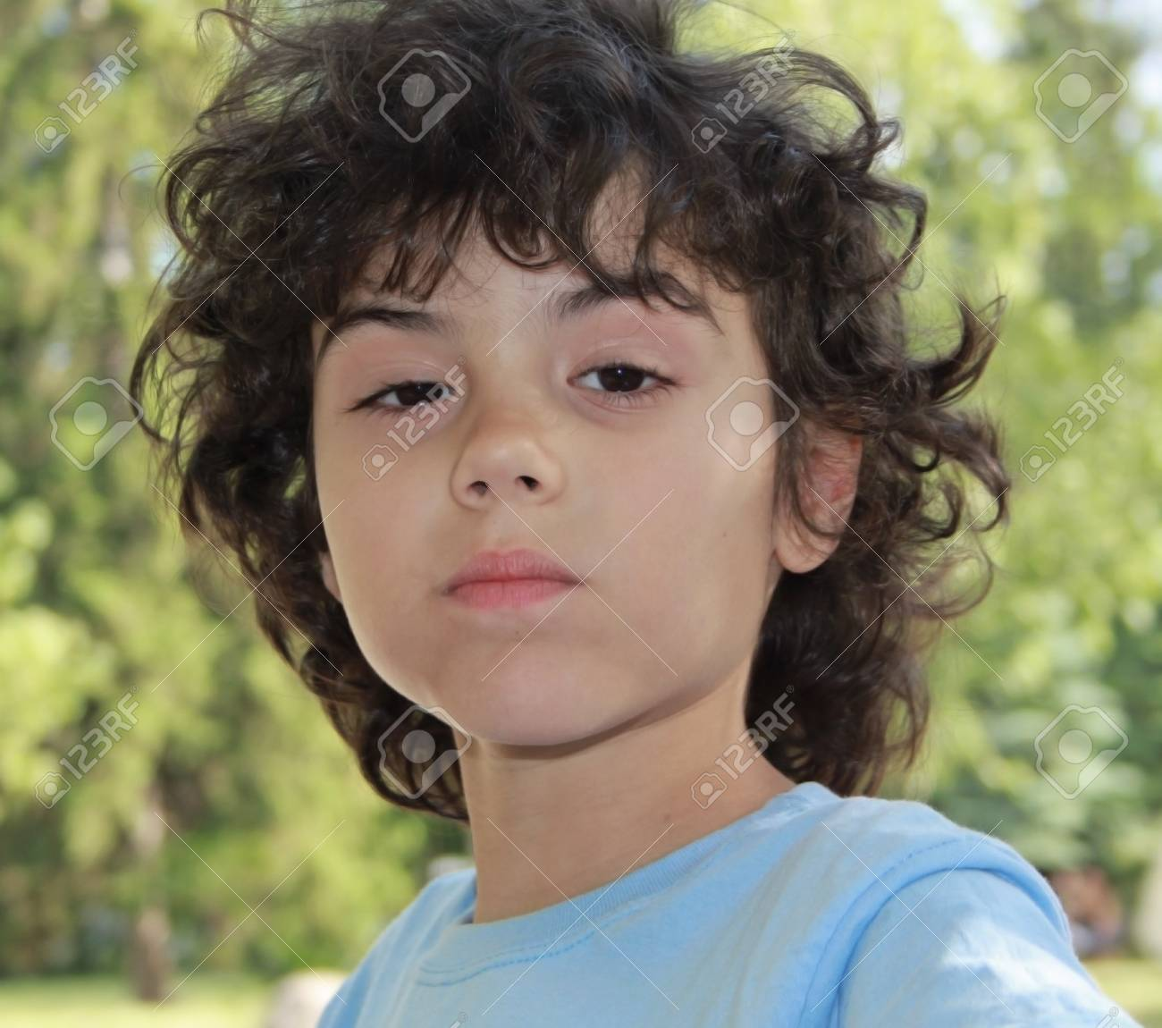 Cute Little Boy With Curly Hair Is Posing In Front Of Camera Stock Photo Picture And Royalty Free Image Image 20082389