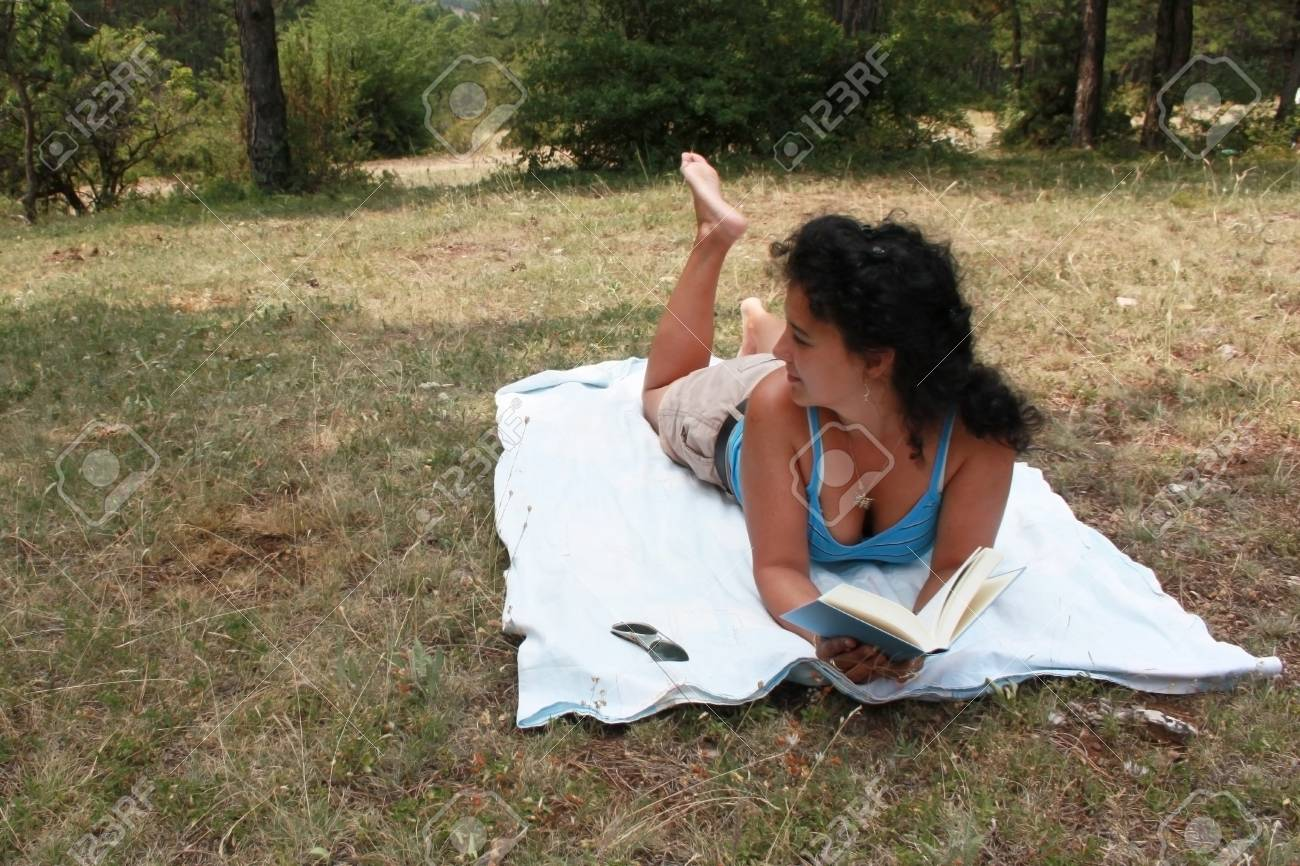 Young brunette is reading a book outdoor Stock Photo - 21648755