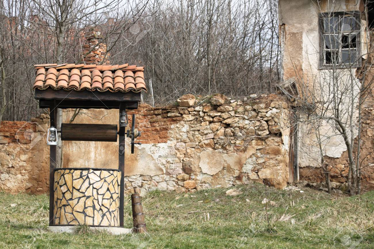 Abandoned house and an old draw well near it in Bulgarian countryside