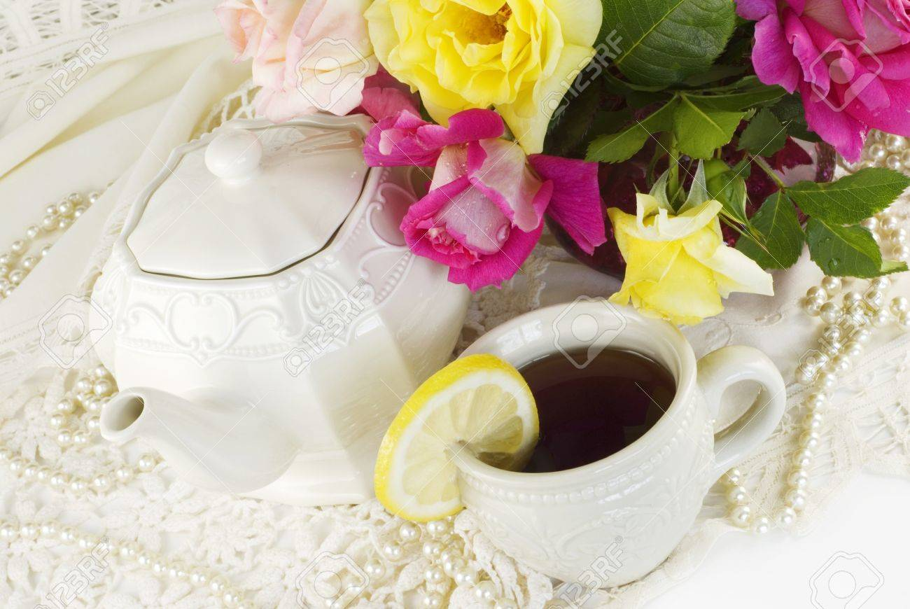 A ladies tea party decorated with antique lace, pearls and fresh garden roses, horizontal with copy space Stock Photo - 8993931
