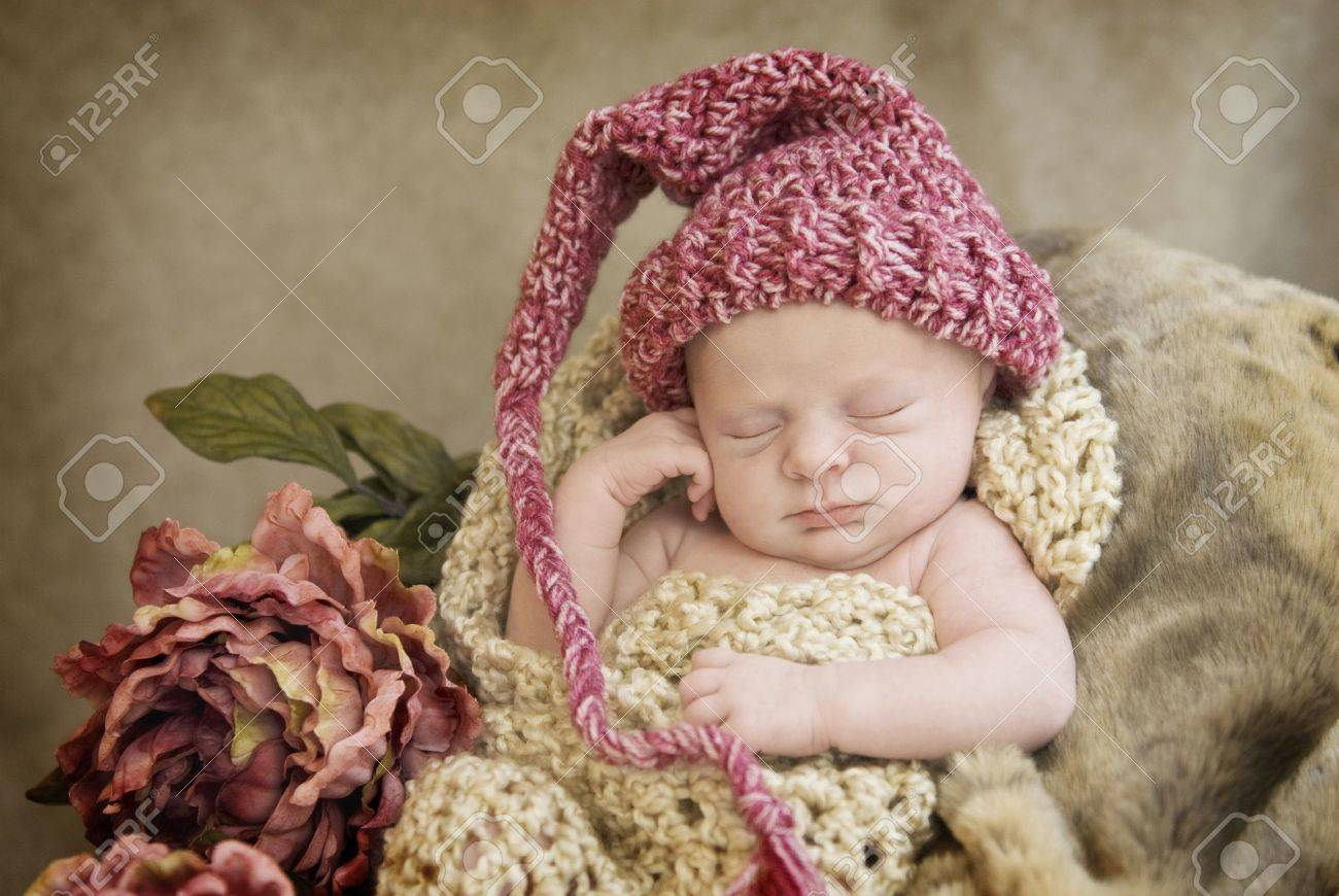 371fb255a6d A sleeping newborn baby girl in chocetted cocoon wearing hat with vintage  looking setup