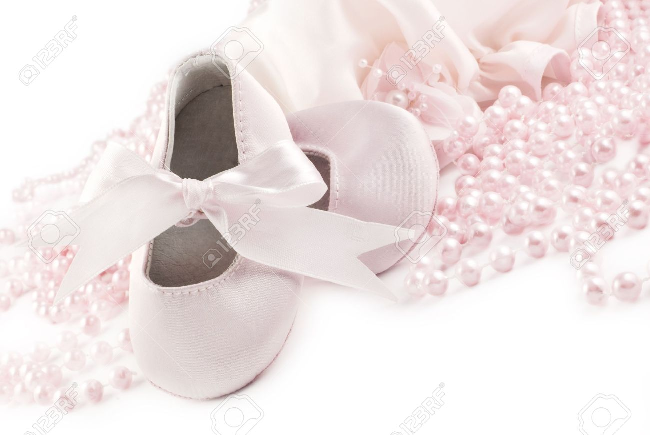 0edd15bb3b14 A pair of pink baby shoes with pink pearls on a white horizontal background  with copy