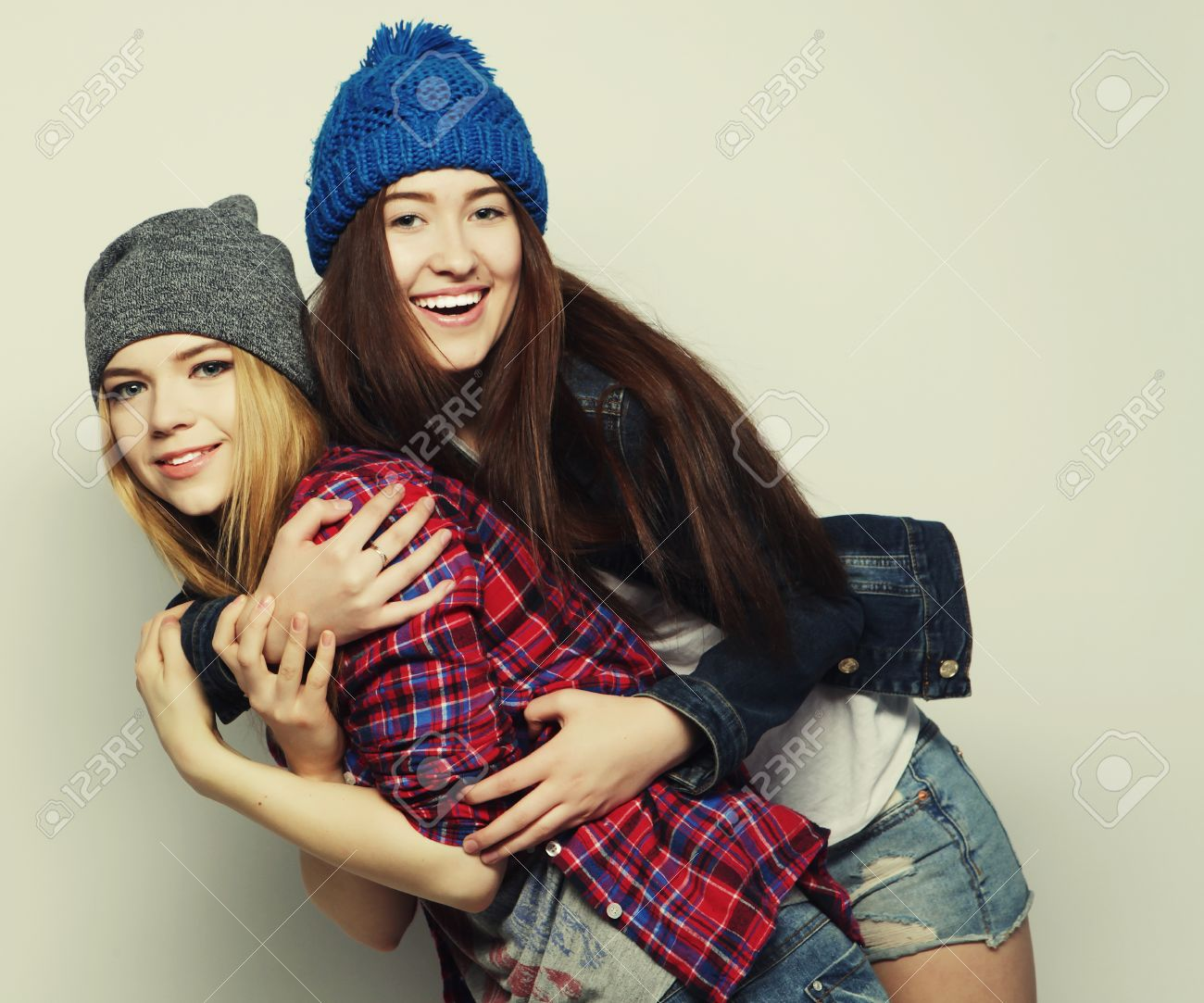 Fashion portrait of two stylish sexy hipster girls best friends, wearing cute swag outfits and