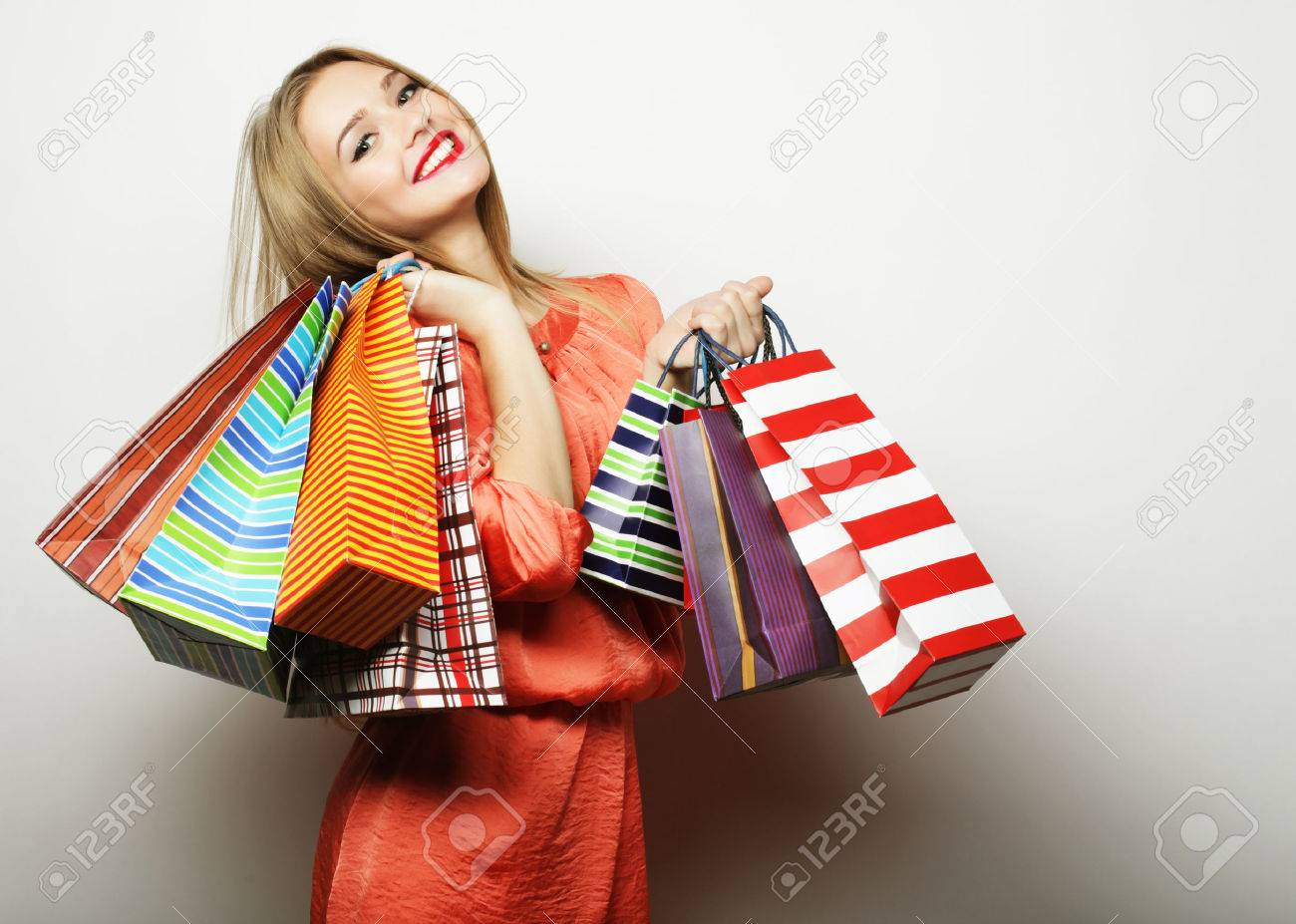 Portrait of young happy smiling woman with shopping bags, over white background - 50259224