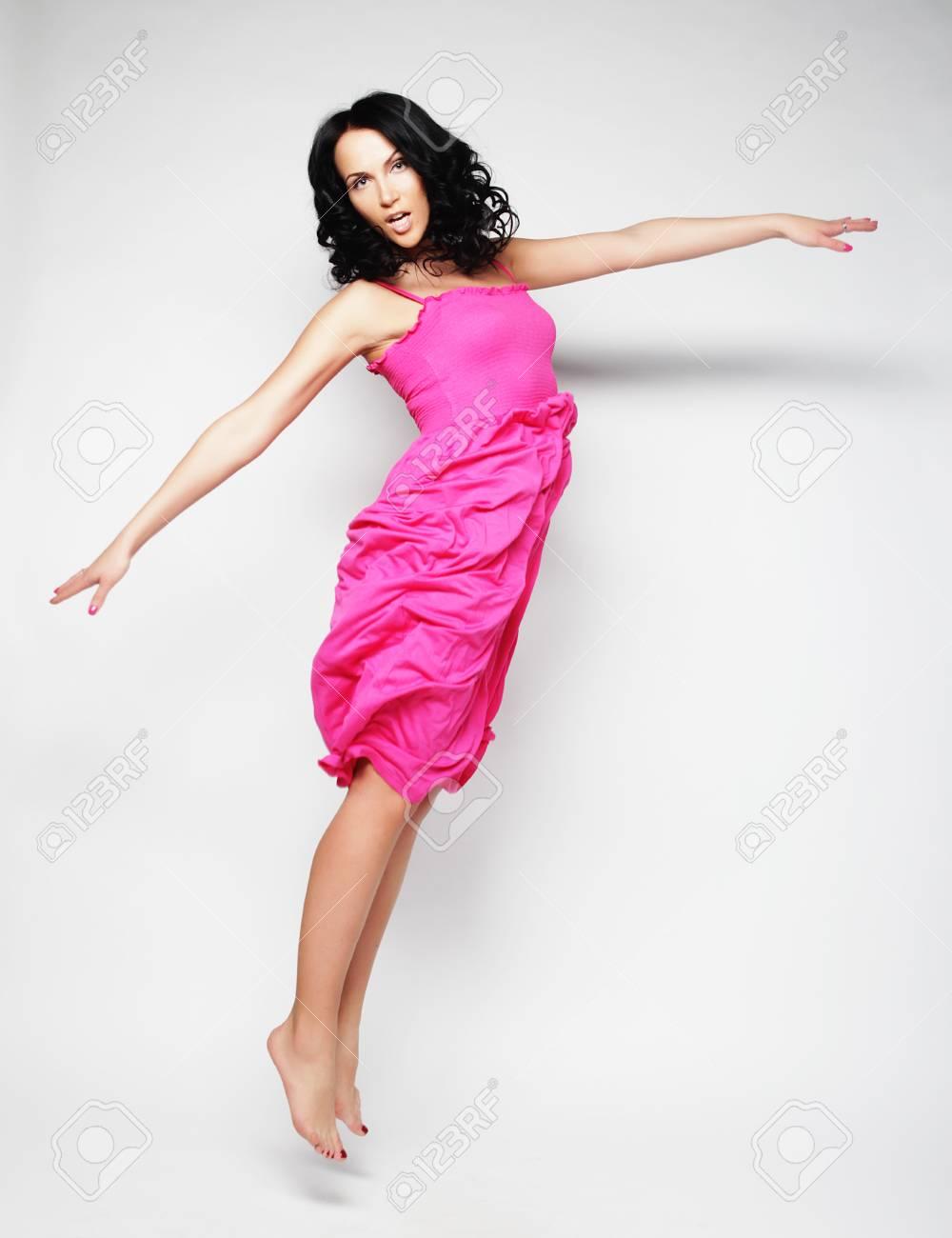 Salto De La Mujer. Emocional Niña Feliz Con Un Vestido De Color Rosa ...
