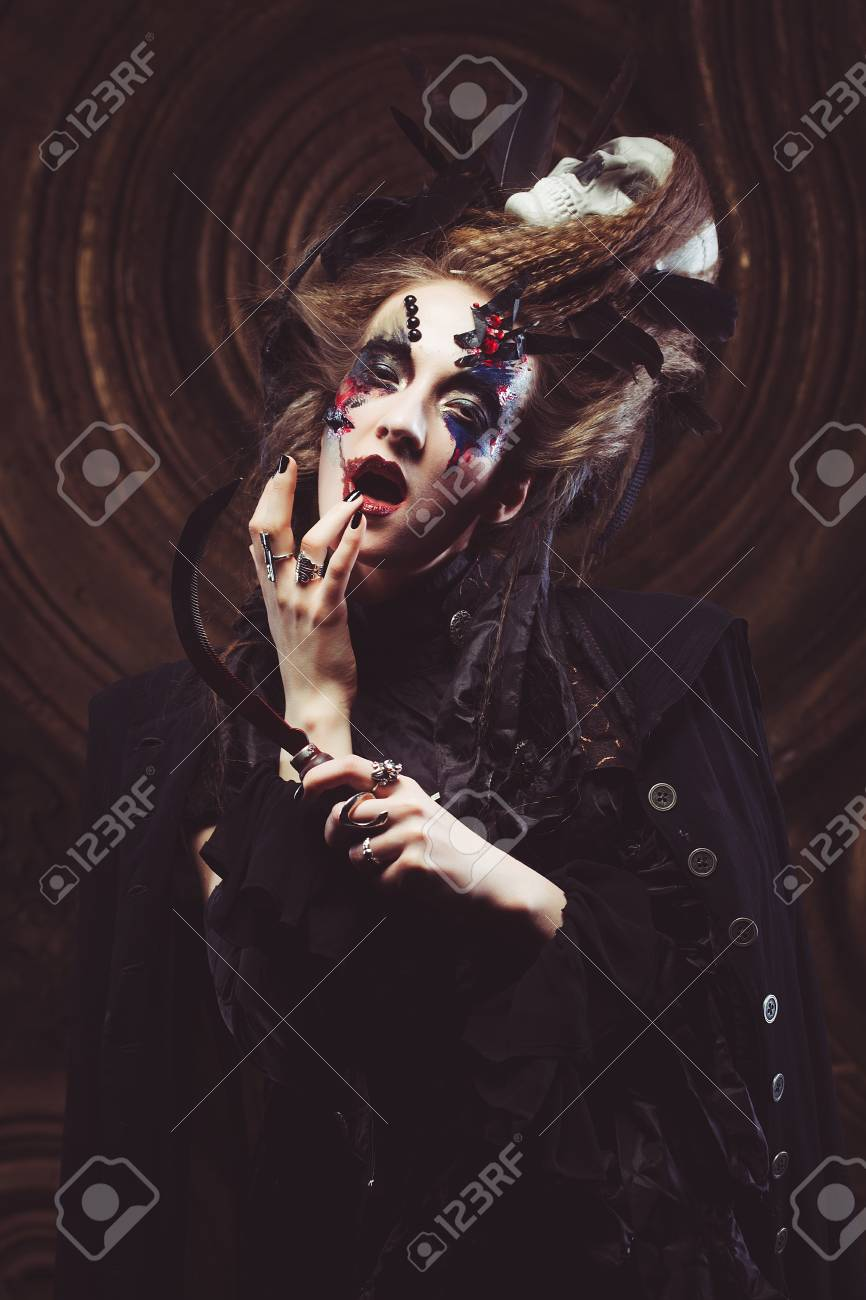 Young witch hloding sickle  Bright make up, skull, smoke- halloween