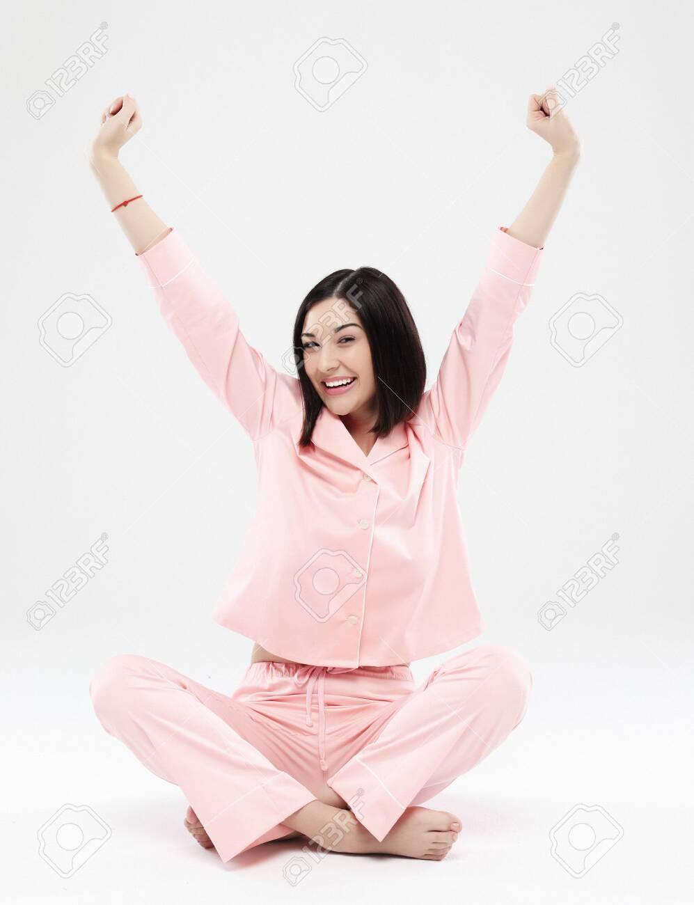 beautiful brunette woman dressed in pink pajamas sitting on the floor - 127802097