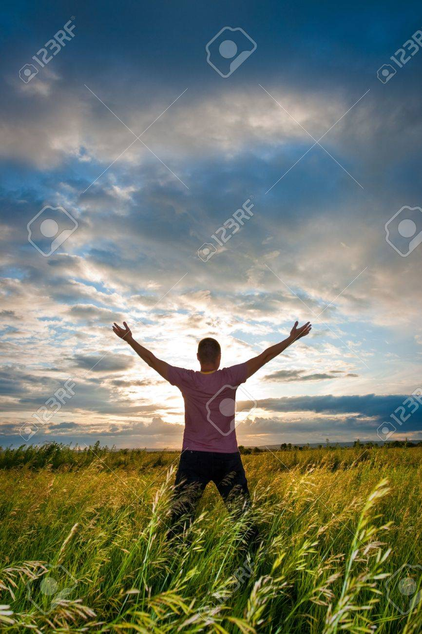 man rising up hands before sunset Stock Photo - 5772993