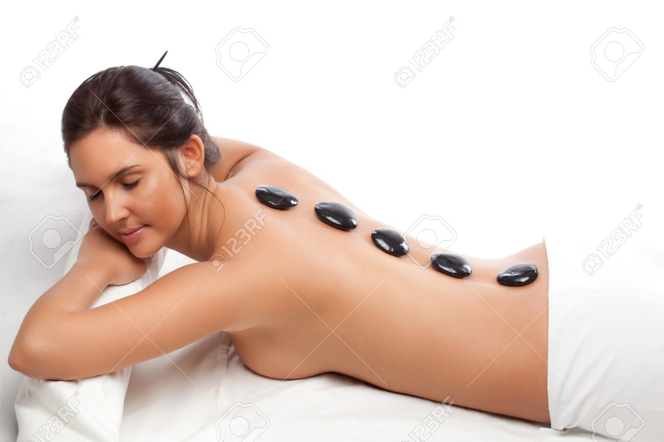 pretty woman receiving a therapy with hot stones in spa center over white Stock Photo - 8736370