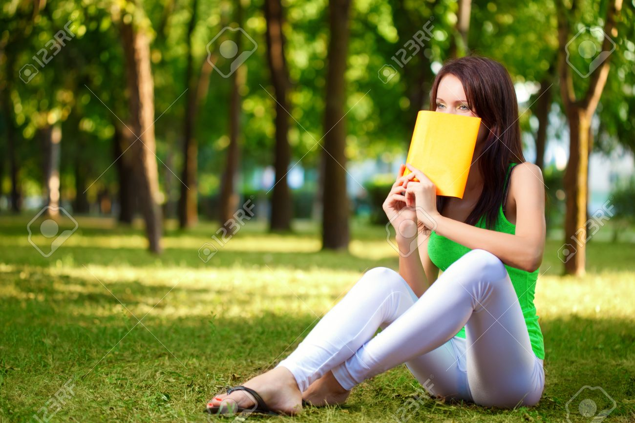 brunette woman cover the face with book at park summer park Stock Photo - 11465068