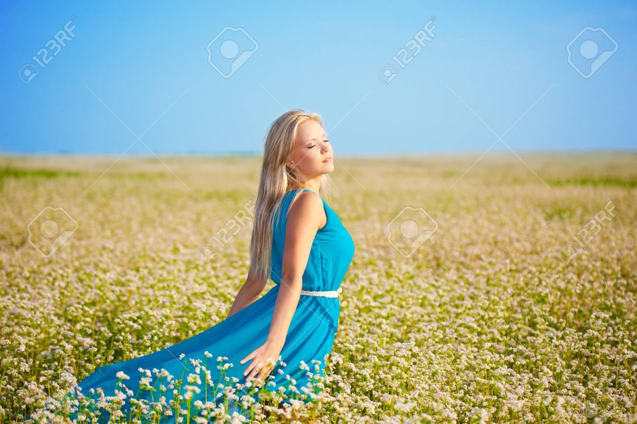 beautiful woman wearing blue dress walking through a field Stock Photo - 15689808