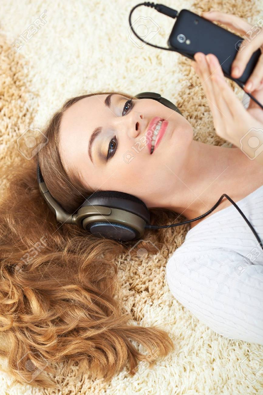 brunette woman lying on carpet and listening to music Stock Photo - 17606857