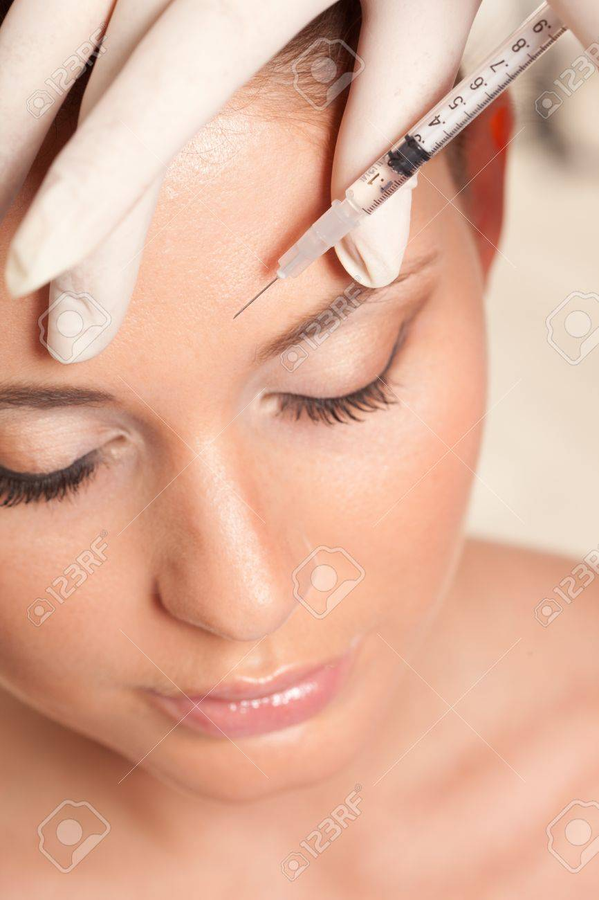 closeup beautiful woman face, syringe injection to forehead, beauty concept Stock Photo - 18387378