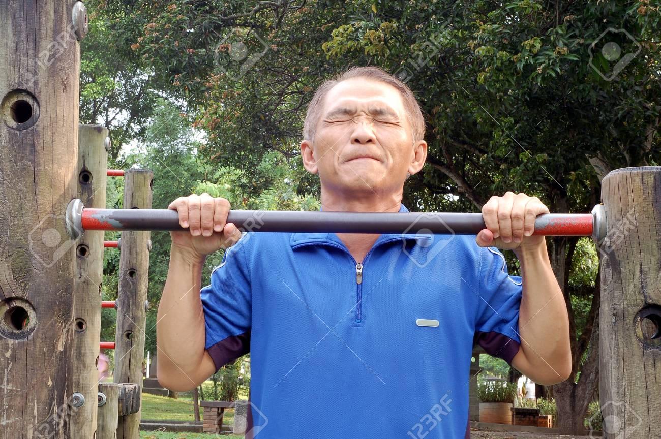 A man who Struggling upwards by Horizontal bar Stock Photo - 15193227