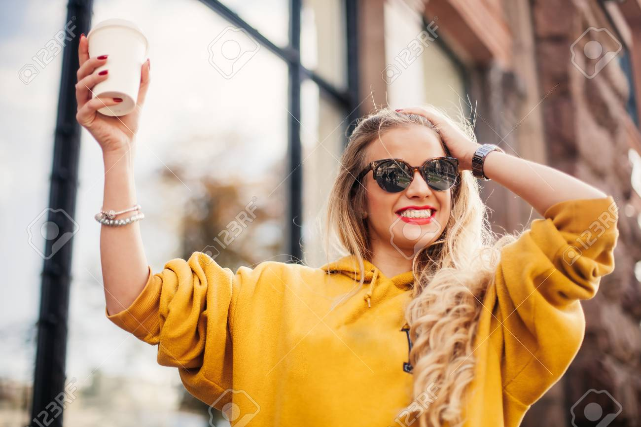 Stylish happy young woman wearing boyfrend jeans, white sneakers bright yellow sweetshot.She holds coffee to go. portrait of smiling girl in sunglasses posing in the street - 89978268