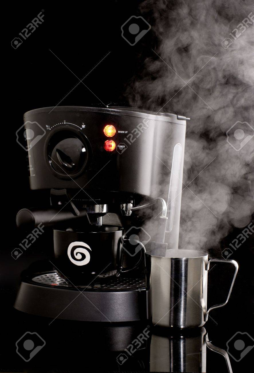Espresso machine in use with frothing cup and steam against black background Stock Photo - 884602