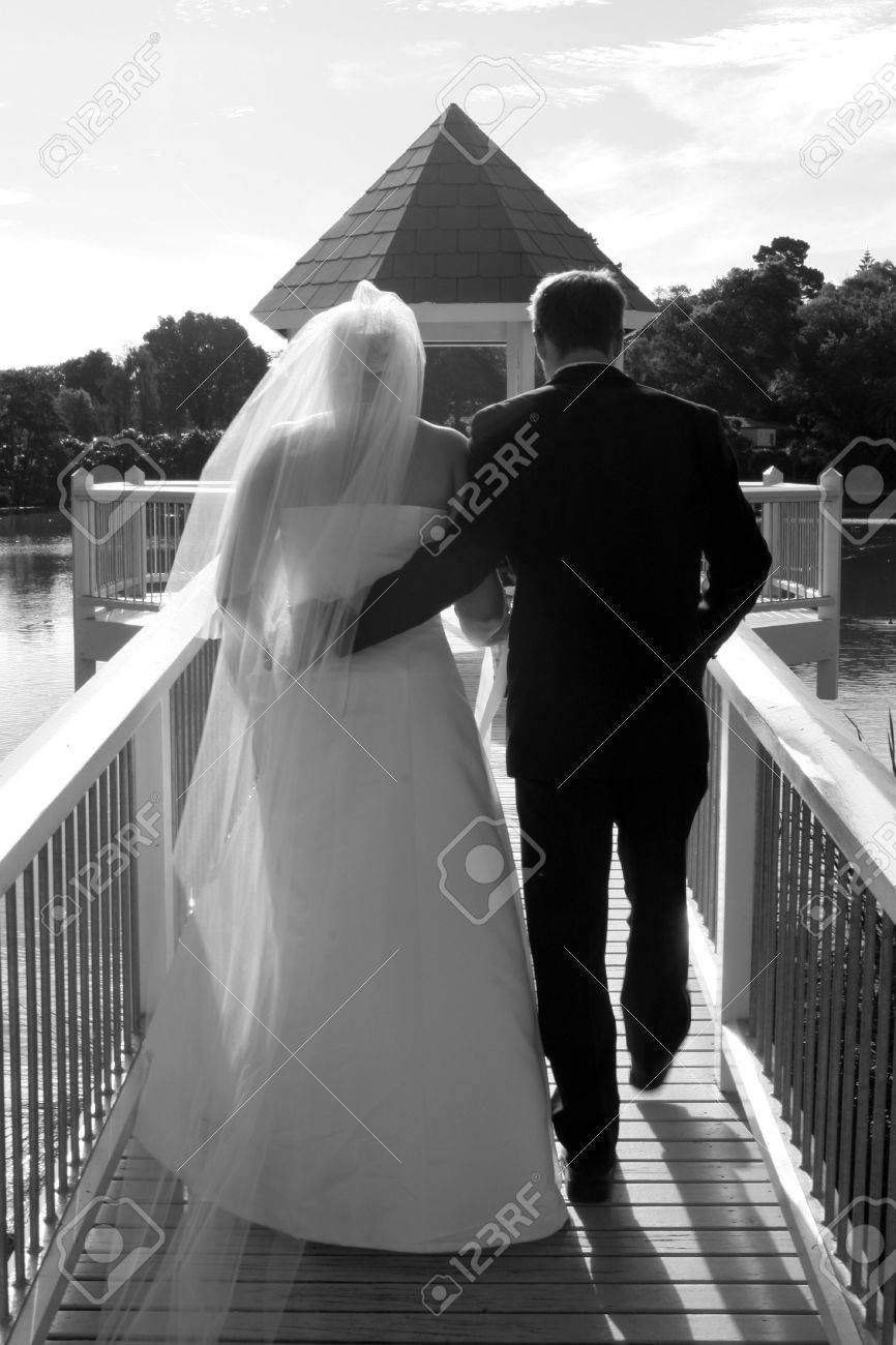Bride and groom walking down a gazebo on a lake Stock Photo - 895732