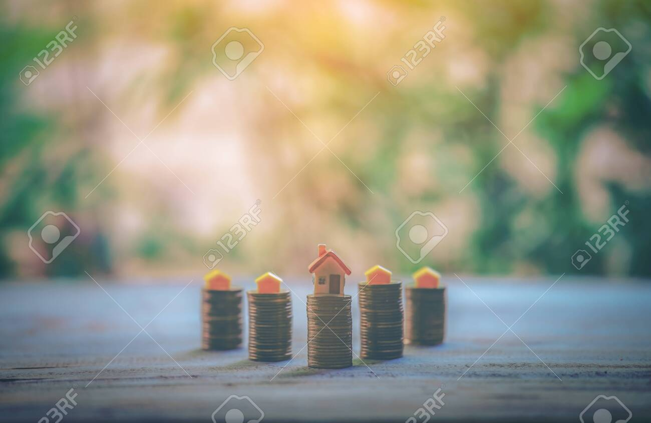 A small house on a pile of coins is used as an asset, financial concept for mortgage, financial investment fund and home loan, interest rate. - 122398356