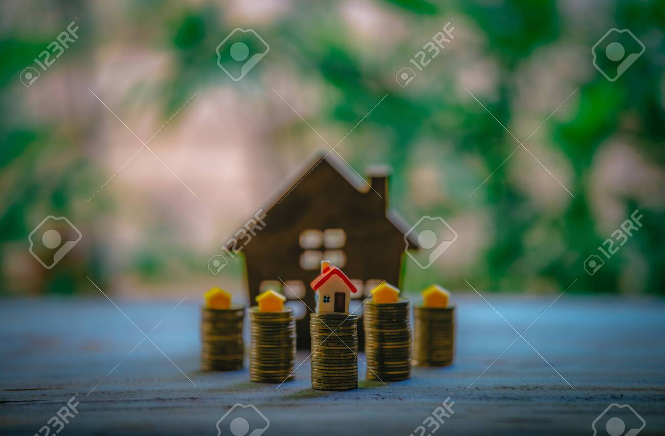 A small house on a pile of coins is used as an asset, financial concept for mortgage, financial investment fund and home loan, interest rate. - 122398359