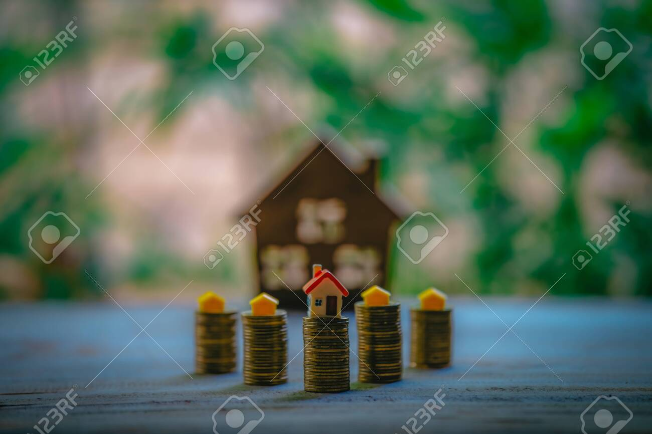 A small house on a pile of coins is used as an asset, financial concept for mortgage, financial investment fund and home loan, interest rate. - 122398360