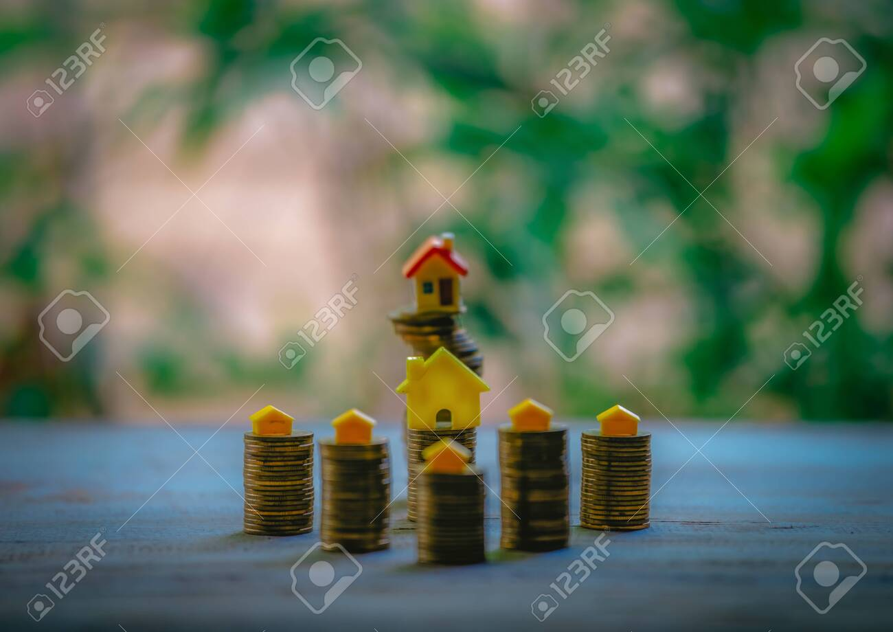 A small house on a pile of coins is used as an asset, financial concept for mortgage, financial investment fund and home loan, interest rate. - 122398362