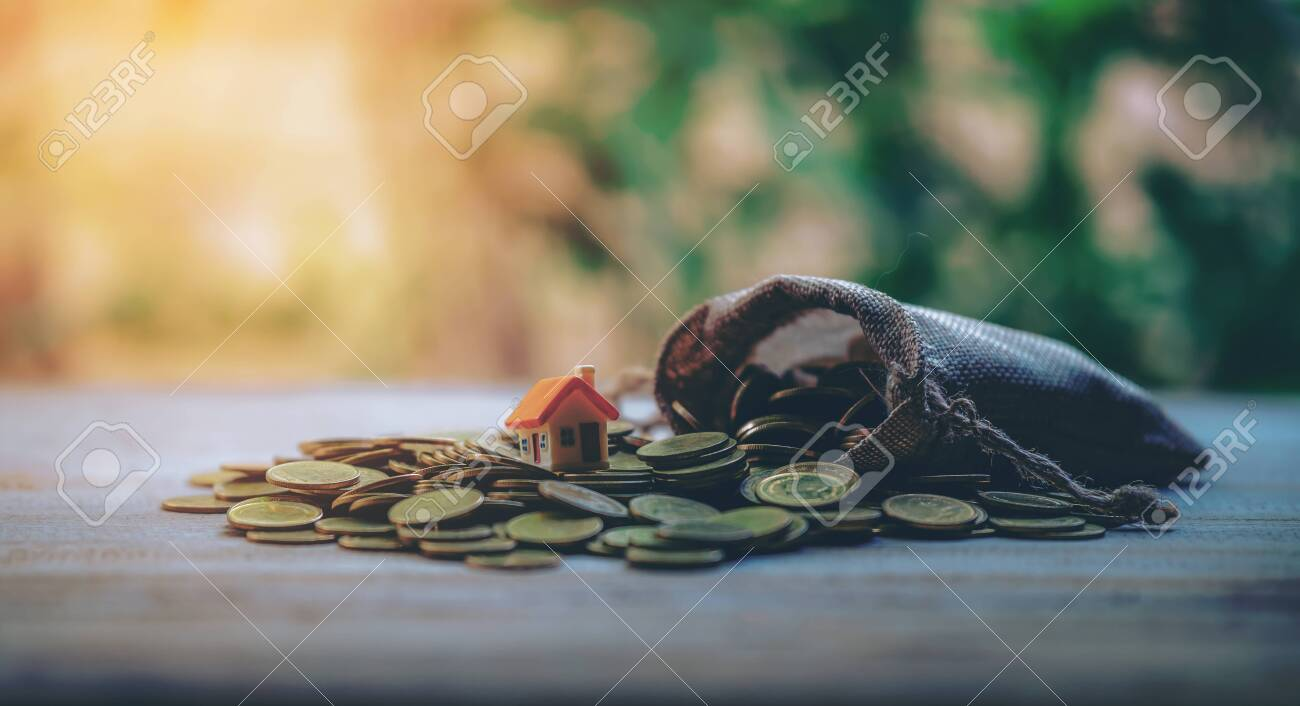 A small house on a pile of coins is used as an asset, financial concept for mortgage, financial investment fund and home loan, interest rate. - 122398211