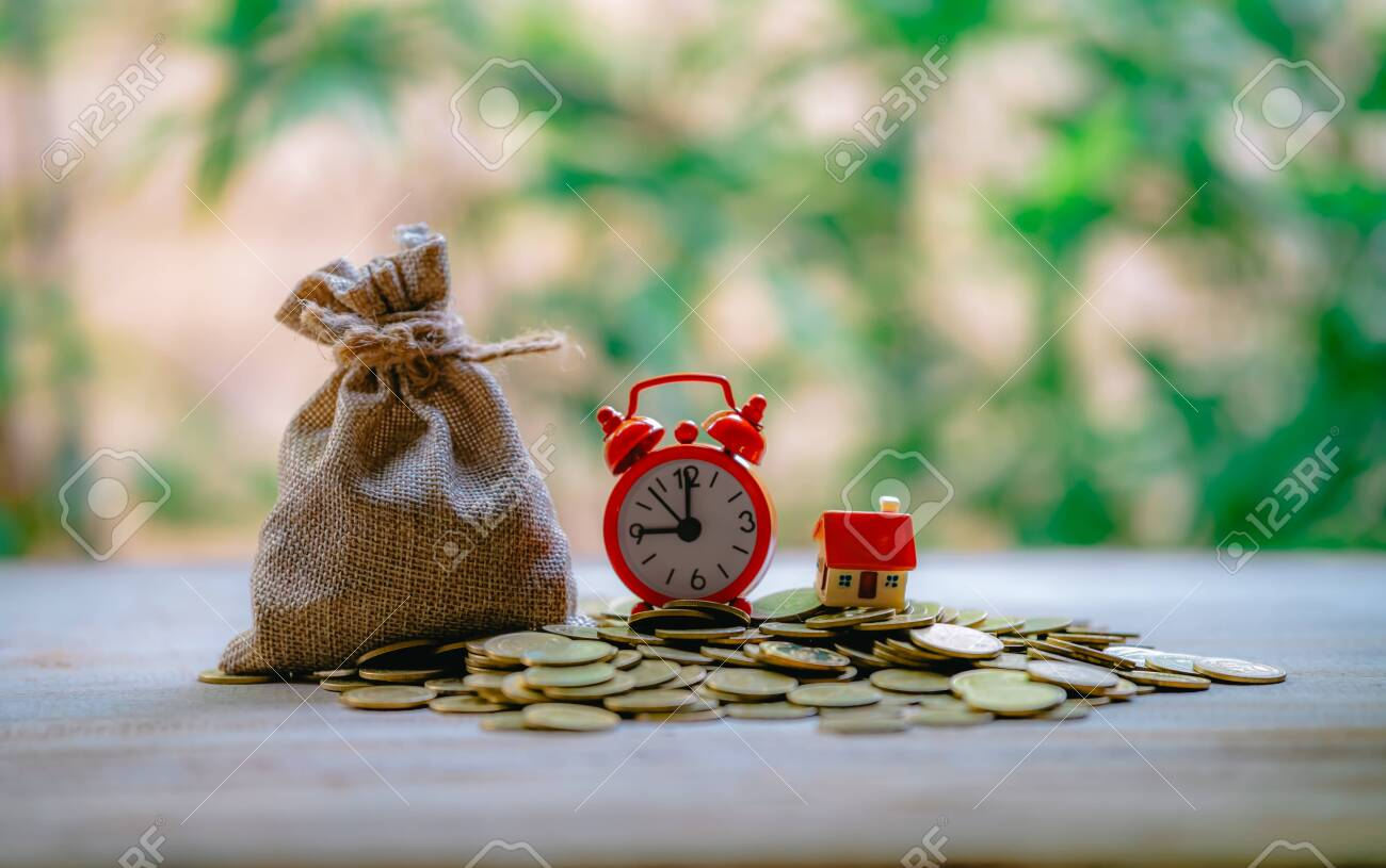 A small house on a pile of coins is used as an asset, financial concept for mortgage, financial investment fund and home loan, interest rate. - 122398212