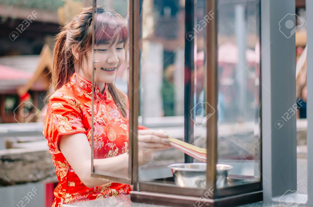 Cute chinese girl dressing traditional red Cheongsam suit burning