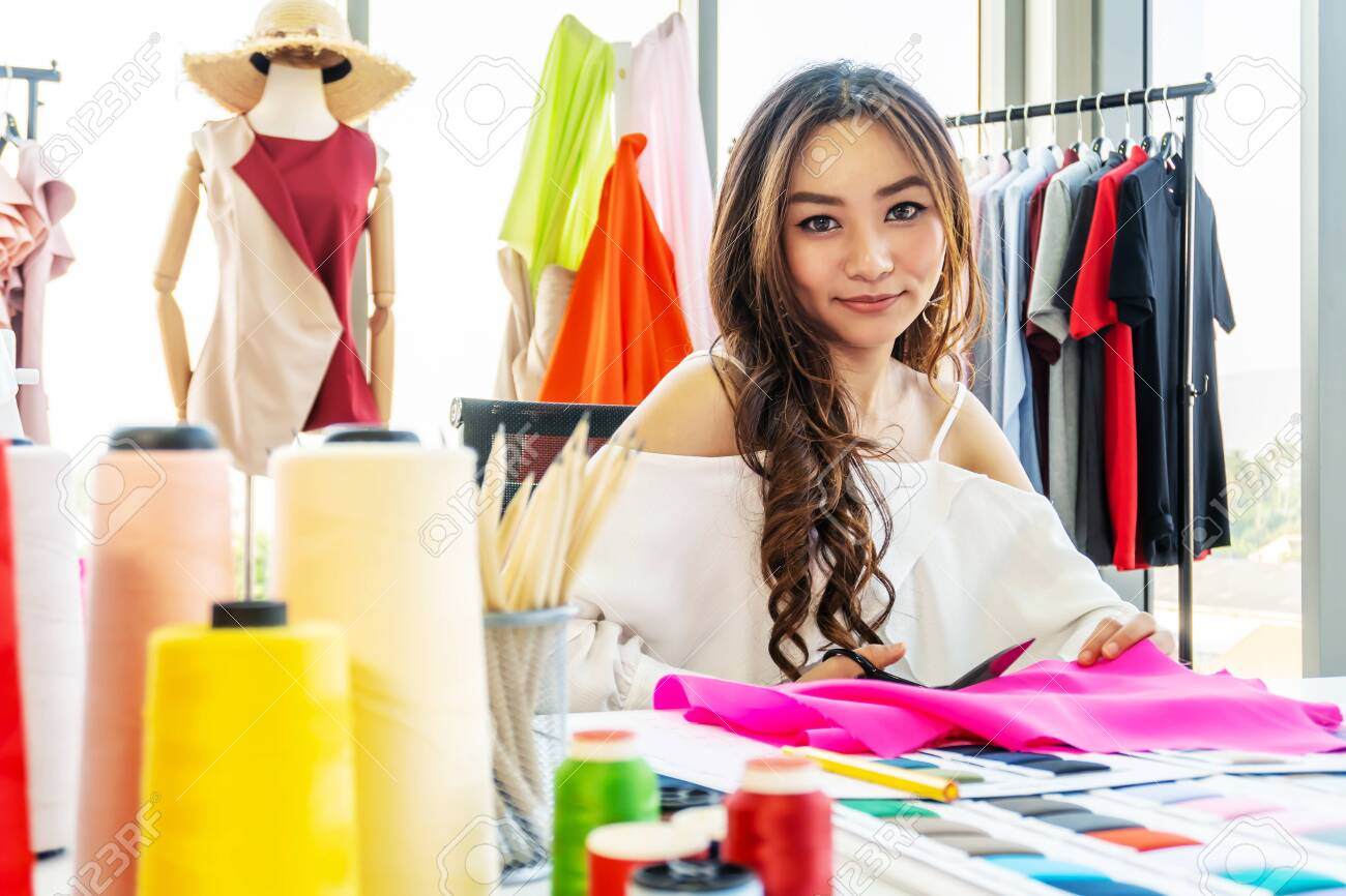 Portrait Of Smiling Fashion Designer Cutting Fabric On Sketch Stock Photo Picture And Royalty Free Image Image 142694755