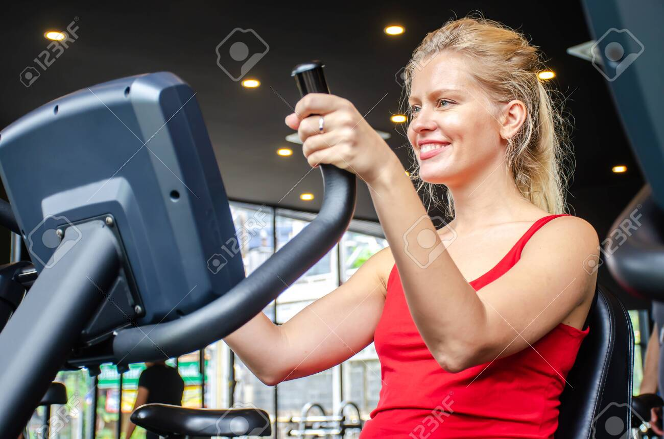 Portrait of young woman exercising using stationary bike in gym, Fitness class doing sport biking in the gym for health. - 149645378