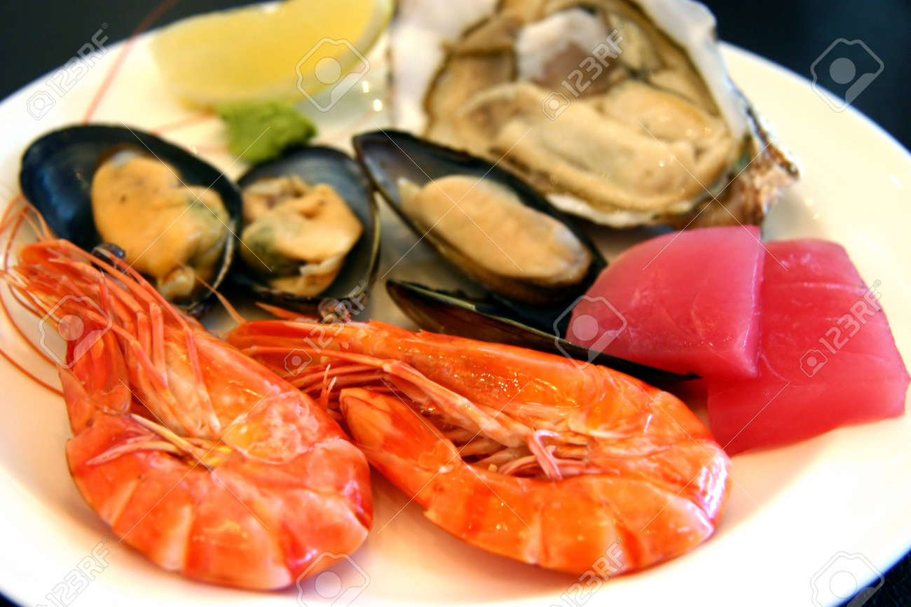 Cold platter of seafood; baked prawns, mussels, oyster and tune sashimi, with some wasabi and wedge of lemon Stock Photo - 369409