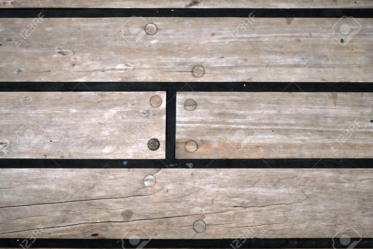 A wooden floor with screws and rubber sealing on the deck of a wooden floor with screws and rubber sealing on the deck of a ship stock photo baanklon Gallery