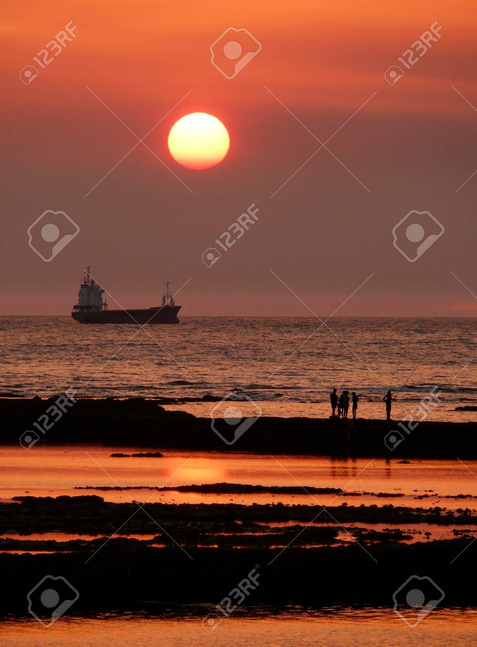 sunset with fishermen on the shore and boat Stock Photo - 19259991