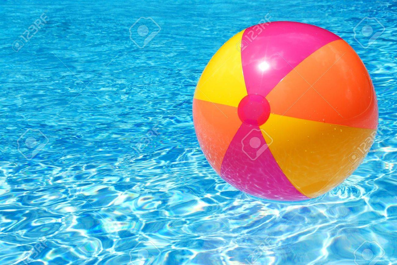 A Colorful Beach Ball Floating On The Swimming Pool Stock Photo