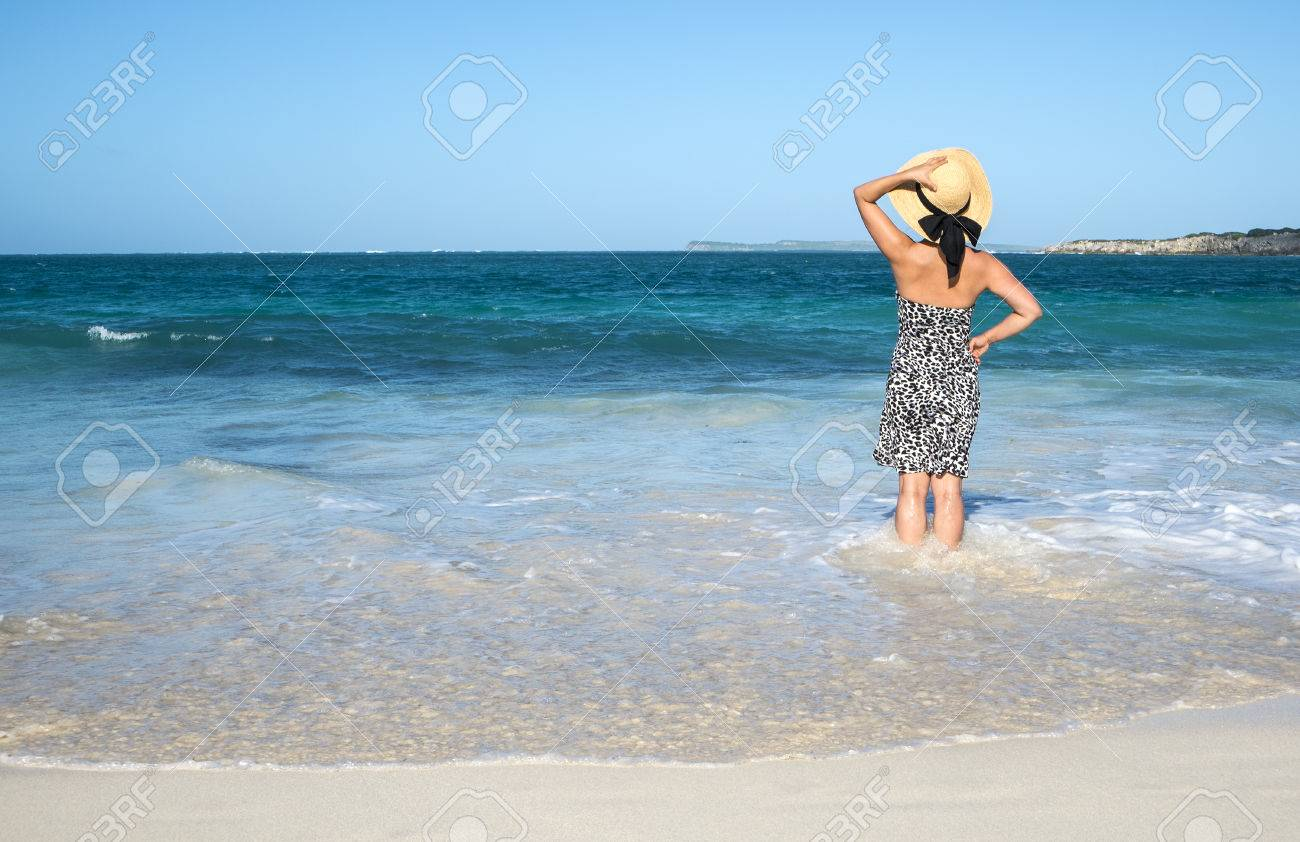 Woman with Straw Hat Looking Out to the Caribbean Sea Stock Photo - 24736535