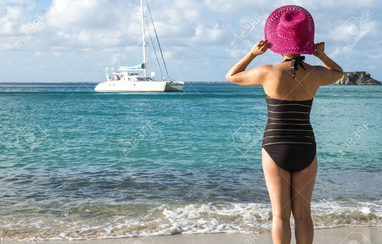Woman with Pink Straw Hat Looking Out to the Caribbean Sea Stock Photo - 24736550
