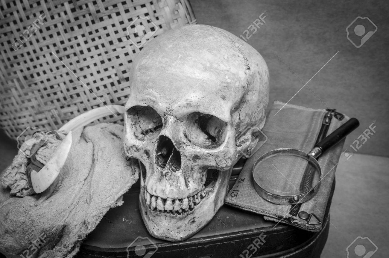 Still life with human skull with old items in black and white