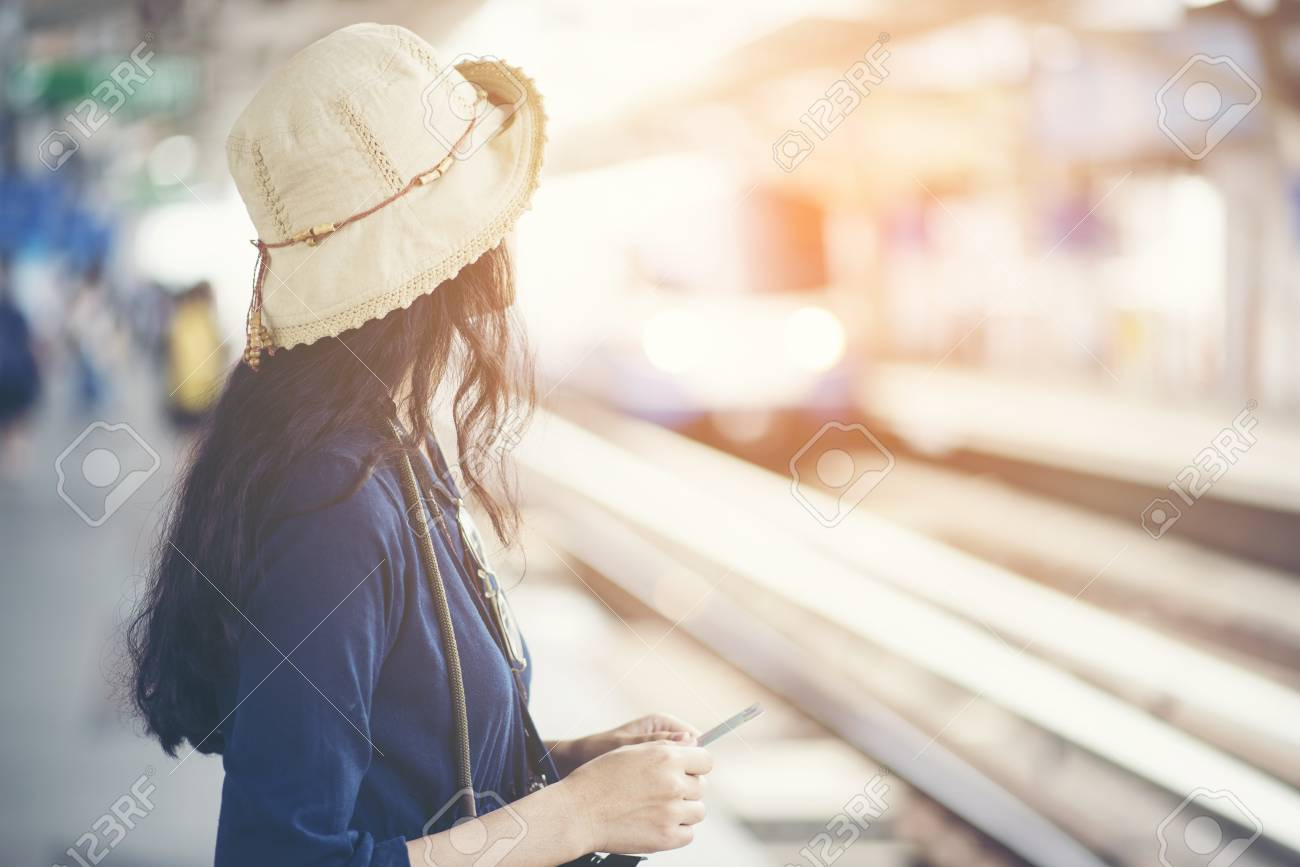 Asian girl waiting train at skytrain station for travel in the big city, lifestyle and transportation concept - 123288987
