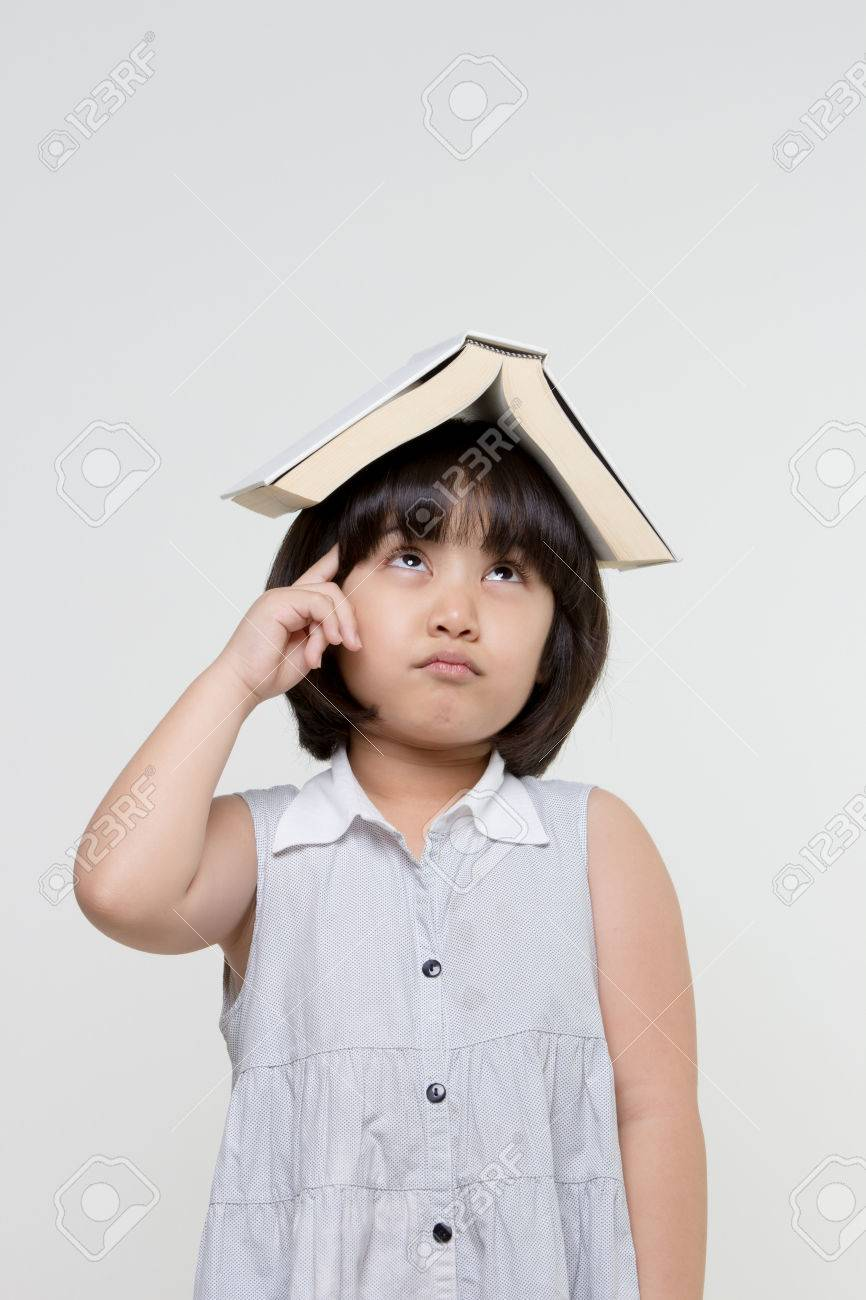 Portrait of little Asian child thinking and put a book on top with copy  space Stock