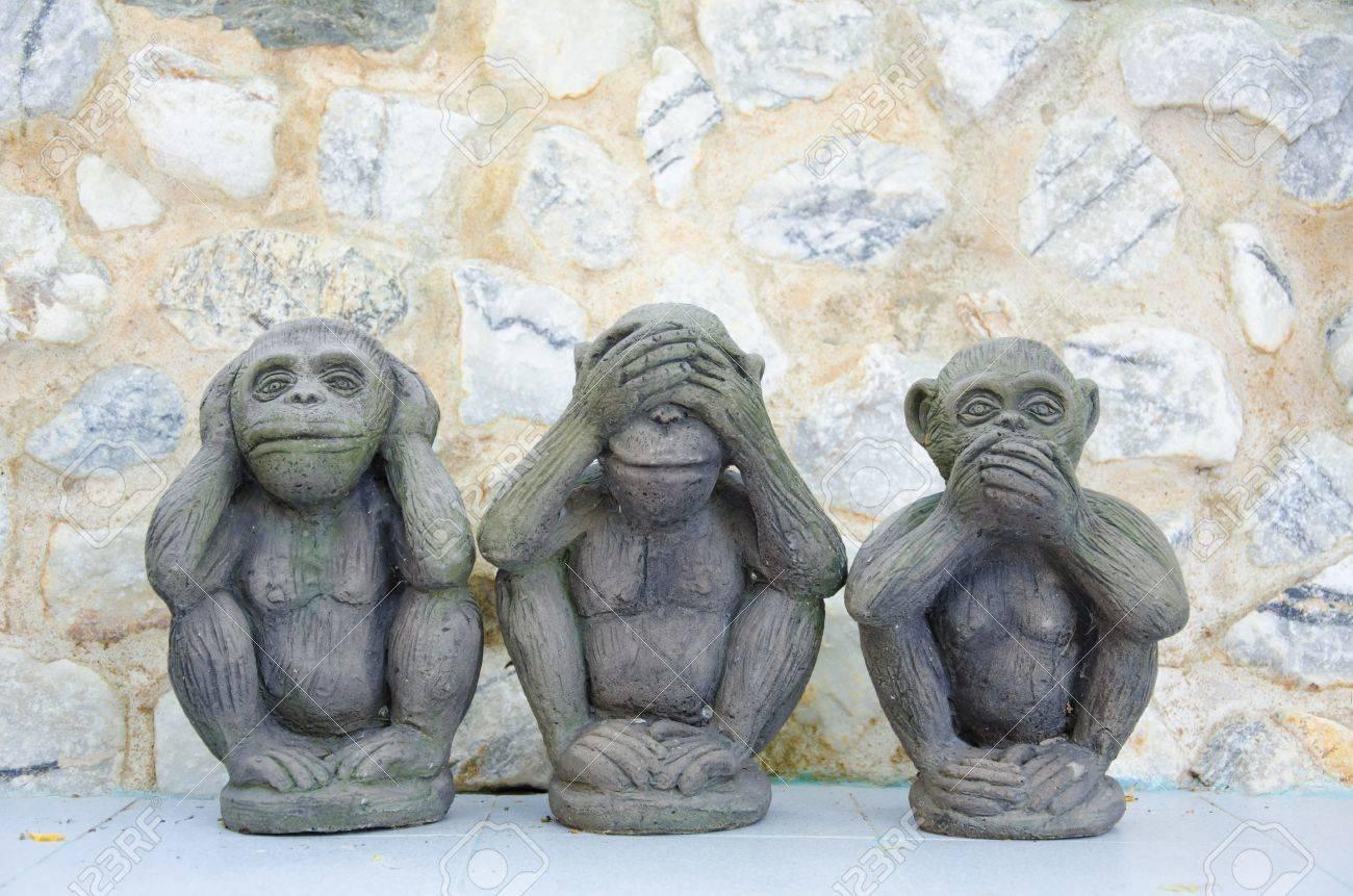 Three wise monkeys wooden ornaments - Monkey Figurine Three Wise Monkeys With Stone Background Stock Photo
