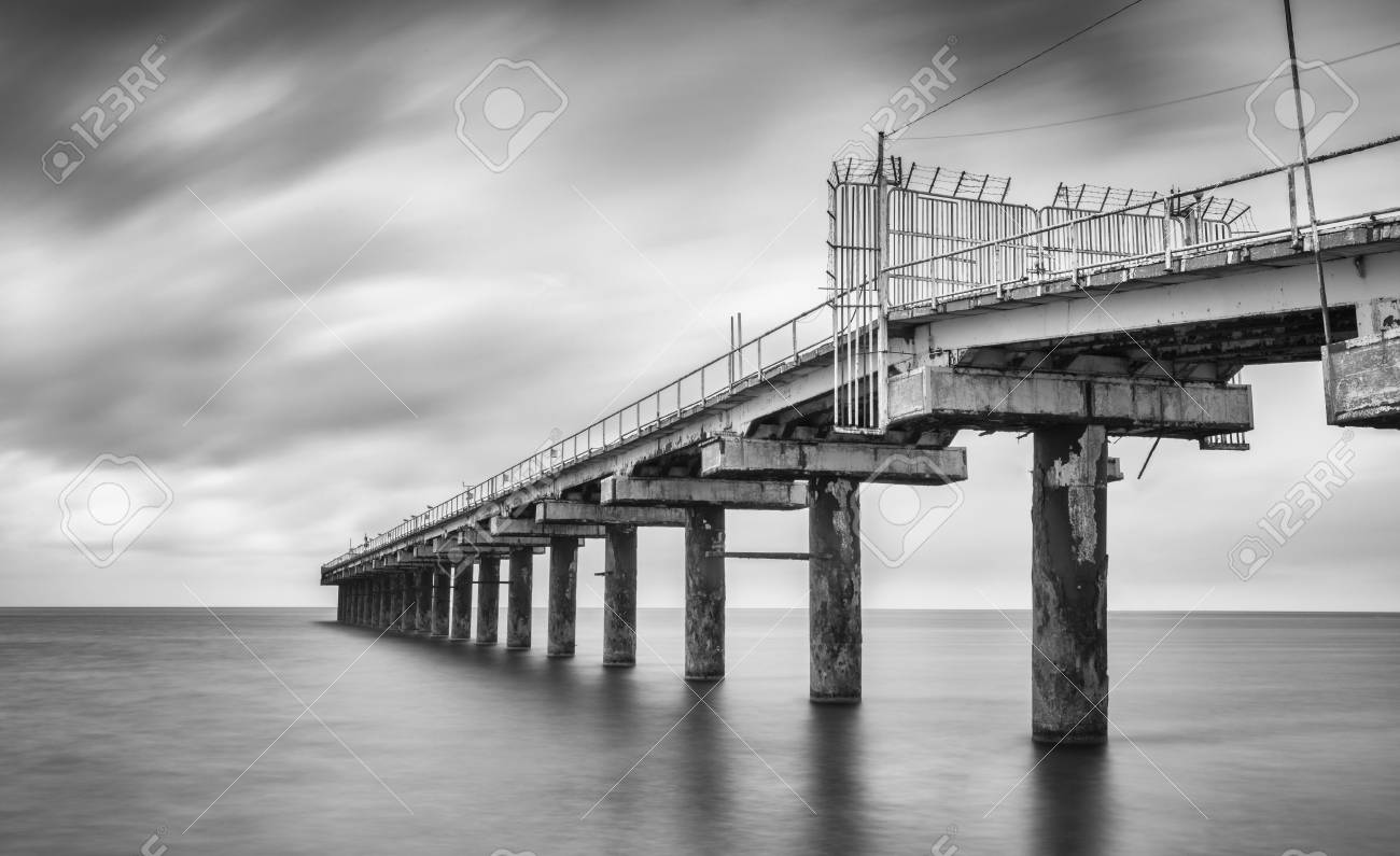 Black and white photo of beach pier long exposure photography